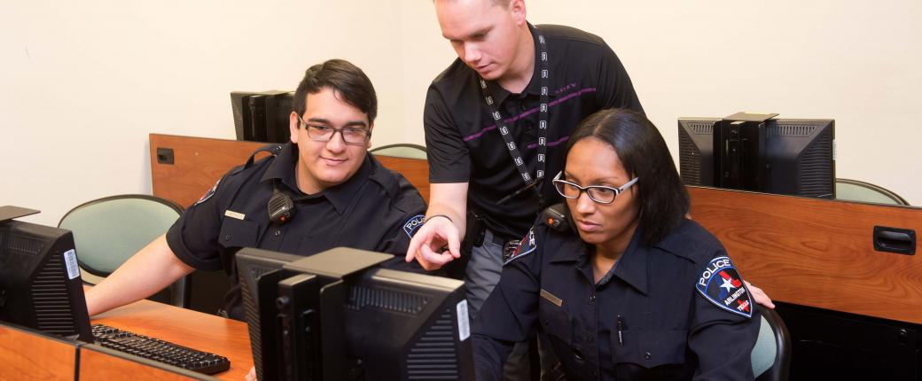 An instructor teaches two trainees on new computer system