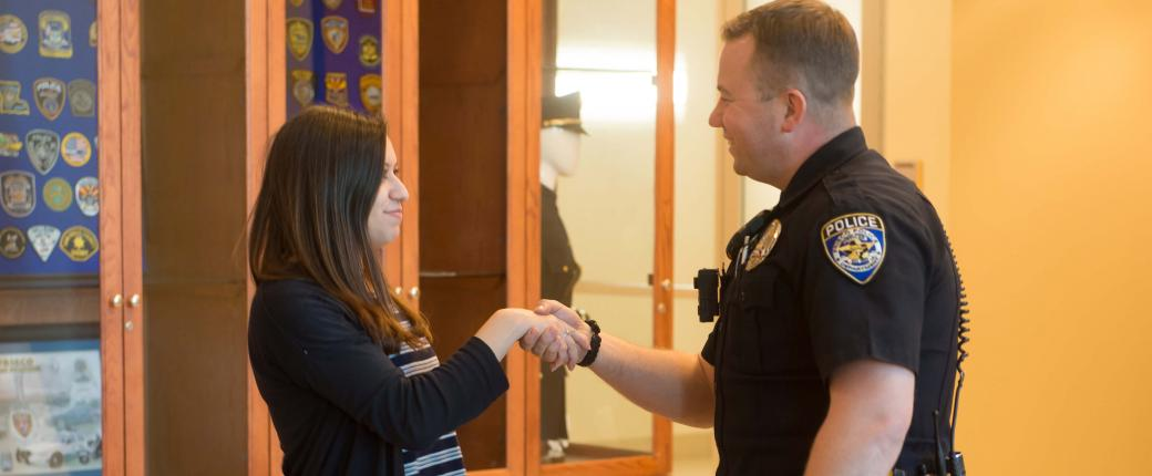 Police officer shaking hands with young woman