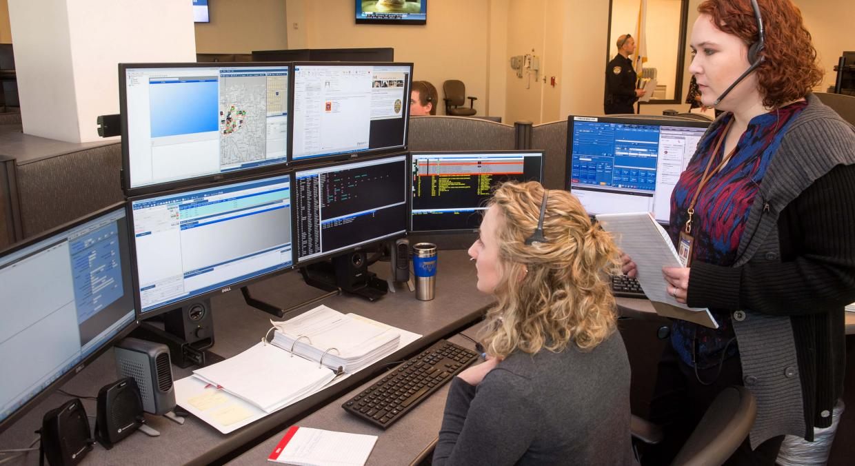 Two staff members overlook a call-center desk and monitors